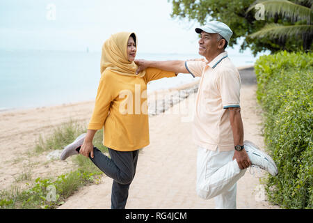 senior man and woman support each other while stretching