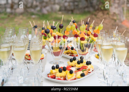 champagne glasses and various snacks for consumption after the wedding ceremony - Stock Photo