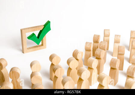 A crowd of people looks at a green check mark. Voting and election concept. Referendum, revolution. Forcible overthrow of power. Democratic process, c - Stock Photo