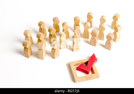 A crowd of people looks at a red check mark. Voting and election concept. Referendum, revolution. Peace and order, legitimization. Forcible overthrow. - Stock Photo
