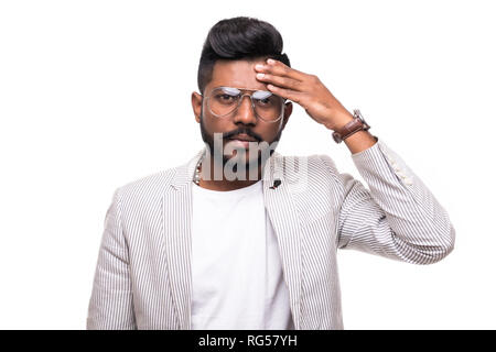 Indian Young man suffering from headache and looks frustrated, isolated over white background - Stock Photo