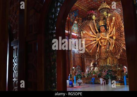 Kanchanaburi.Thailand,Jan 24,2019 ,Take photo buddhist girl and  large Guan Yin Bodhisattva carved from wood 12 meters high in Wat Metta Photiyan , A  - Stock Photo