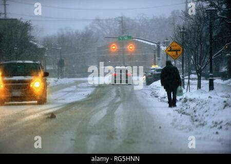 Bartlett, Illinois, USA. A snowstorm impacts Main Street in the Chicago area as a man takes to waling in the street in avoiding snow packed sidewalks. - Stock Photo