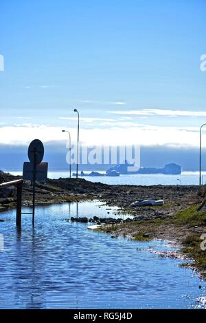 Ilulissat, Greenland, July   midnight sun   impressions of Jakobshavn   road sign - no tresspassing on a flooded road   icebergs in the Disko Bay - Stock Photo