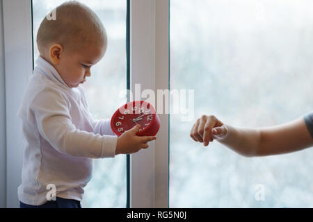 Mother and child are sitting on windowsill. Son holds alarm clock. Winter day outside window. Warmly family relationships. - Stock Photo
