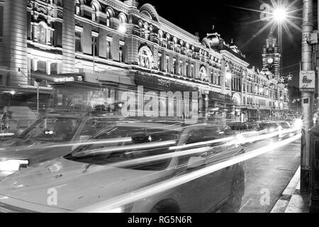Flinders Street Station is a famous landmark and tourist attraction in Melbourne, Victoria, Australia. Shown with tram and vehicle traffic on Flinders - Stock Photo