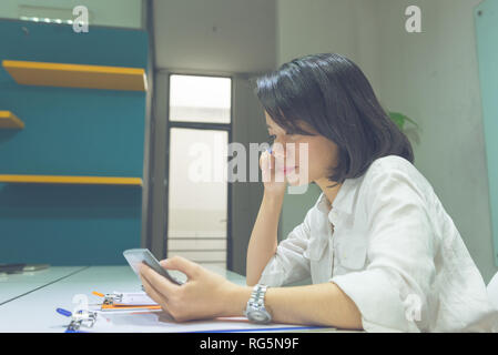 Side view of Asian office lady checking information on sales reports - Stock Photo