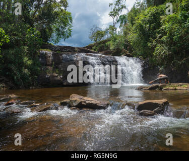 Young woman doing yoga pose in front of Cachoeira do Piu (Piu's Waterfall) near Serra do Brigadeiro mountains, in Minas Gerais, Brazil. - Stock Photo