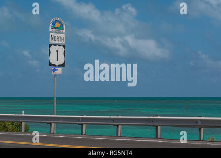 Highway road sign for Florida Scenic Highway North 1, the Overseas Highway to the Florida Keys, with sea and sky in the background. - Stock Photo
