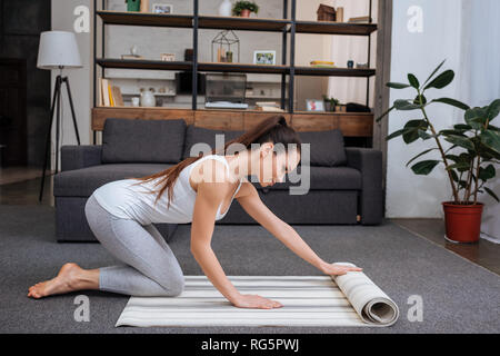 beautiful young woman rolling fitness mat for practicing yoga at home - Stock Photo