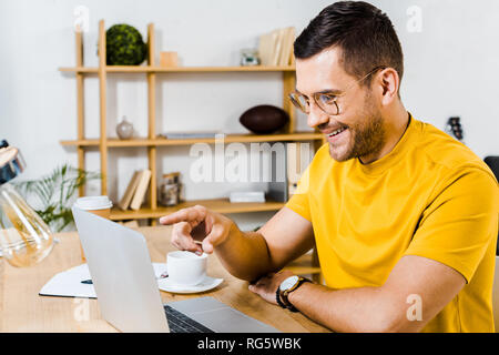 happy man in glasses pointing with finger at laptop - Stock Photo