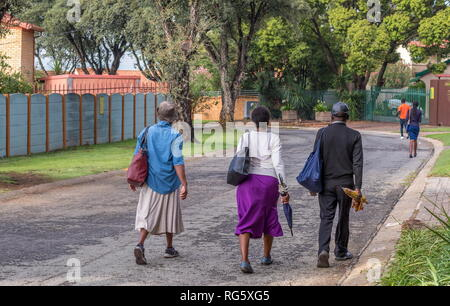 Johannesburg, South Africa - unidentified black laborers walk to work through a residential suburp in the city - Stock Photo