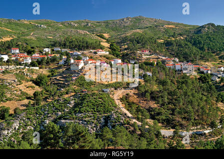 View of mountain village surrounded by green mountains and rocks - Stock Photo