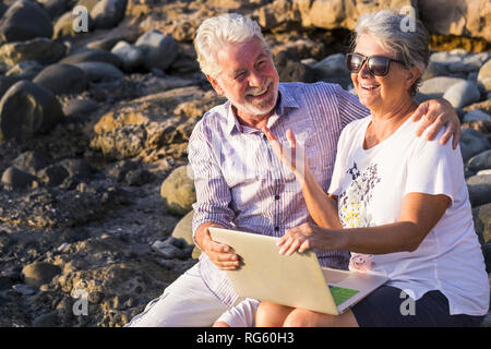 Happy laughing and smiling caucasian cheerful adult mature couple having fun outdoor using technology laptop computer together under the sun in vacati - Stock Photo