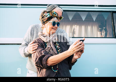 Cheerful old caucasian adult couple using technology smart phone internet to take selfie picture for social media accounts - cheerful people with old  - Stock Photo
