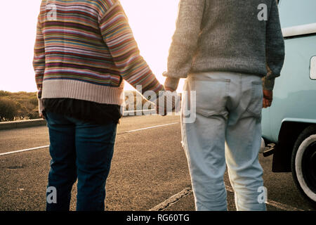 Romantic couple for romiance image concept taking holding hands together in love - defocused blurred image with focus at the end of the road - love an