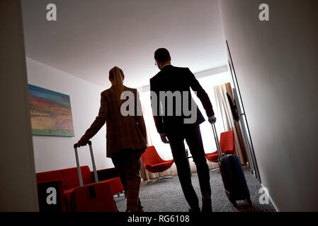 Couple in hotel room at business trip. Two tired business people entering in a hotel room. Rear view - Stock Photo
