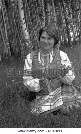 The participant of rural Amateur ensemble is sitting in meadow in the woods. The beautiful girl is dressed in Belarusian national clothes. She holds in her hand wildflowers. Beautiful birch grove is visible behind the actress. - Stock Photo