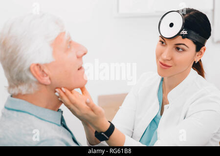 otolaryngologist doctor examining her patient, checking seniors man glands at clinic - Stock Photo