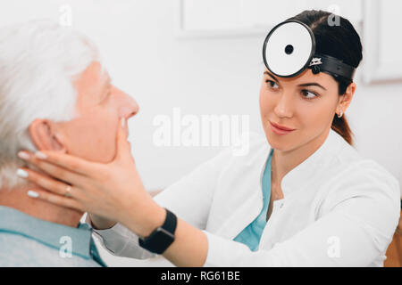 otolaryngologist doctor examining her patient, checking seniors man nose at clinic - Stock Photo