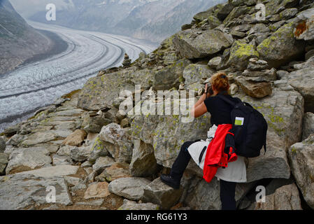 Woman taking a photo of the Great Aletsch Glacier, Valais, Switzerland - Stock Photo