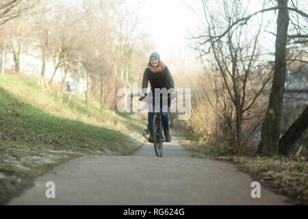 Woman cycling along a footpath by the river, Germany - Stock Photo