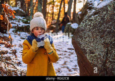 Girl standing in the forest eating a piece of ice, United States - Stock Photo