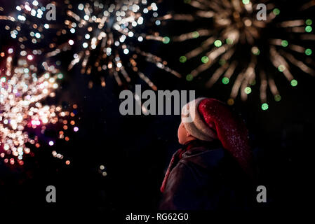 Rear view of a boy watching a firework display - Stock Photo