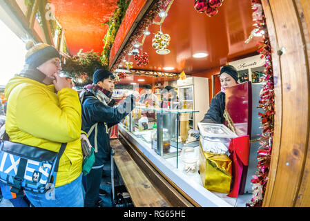 Vienna Austria December 26 ,2018: Visitors to Vienna Christkindlmarkt Christmas Market stand in front of a stand selling various traditional sausages - Stock Photo