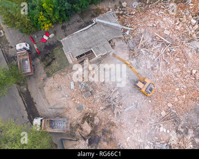 yellow excavator on demolition site working on old building and loading debris into dumper trucks. aerial view - Stock Photo