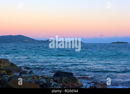 Sunset over Caribbean Sea with Virgin Islands US on horizon. Sun goes down behind mountainous landscape of St. Thomas island. - Stock Photo