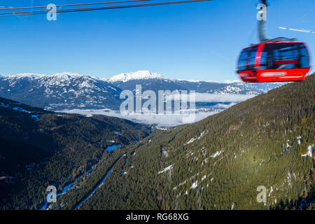 A large gondola car streaking by with the valley in between Whistler and Blackcomb in the background. - Stock Photo