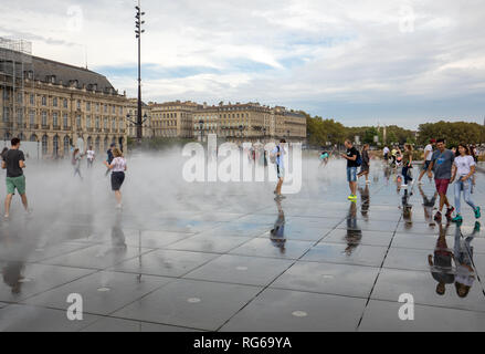 Bordeaux, France - September 9, 2018: Fog effect at The Water mirror in front of the Stock Exchange Square (Place de la Bourse), Bordeaux, France - Stock Photo