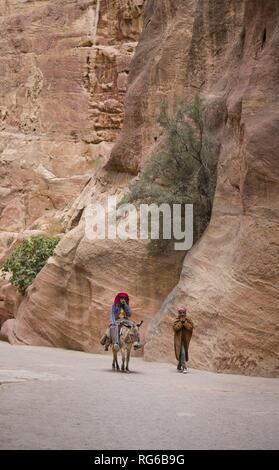 The access to the rock town Petra leads through a narrow entrance (Siq).  The reddish rock walls rise up to 100 meters.  (05 November 2018) | usage worldwide - Stock Photo