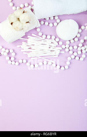 Branch of cotton plant, eared sticks, cotton pads, towel, cosmetic makeup removers tampons, hygienic sanitary swabs  on purple background Top view. Sp - Stock Photo