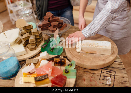 Shop assistant cutting bars of natural soap for customer in package free store. Display of colorful handmade organic soaps in packaging free shop. - Stock Photo