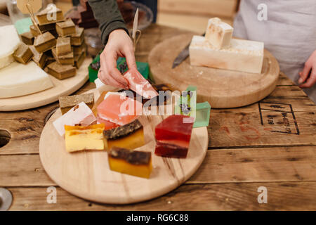 Customer picking from various natural soap bars in packaging free store. Zero waste shop. - Stock Photo