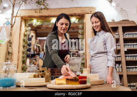 Cheerful shopkeeper helping customer in packaging free shop. Zero waste shopping - woman choosing natural homemade soap at package free store. - Stock Photo