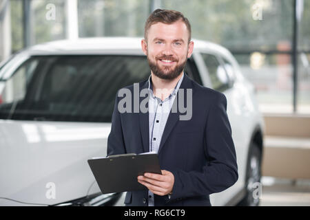 Handsome manager of modern car dealership holding black folder in hands. Bearded man looking at camera, smiling, standing near white auto. Car dealer wearing in dark blue jacket and shirt. - Stock Photo