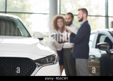 Close up of white car headlight. Happy couple standing near car dealer. discussing purchase of vehicle. Manager in dark blue jacket holding keys and black folder, showing documents.  - Stock Photo