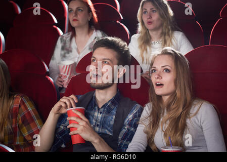 View of shocked couple looking at screen in cinema theater with opened mouth. pretty blonde girl in gray and handsome man enjoying scary movie. Concept of friends and free time. - Stock Photo