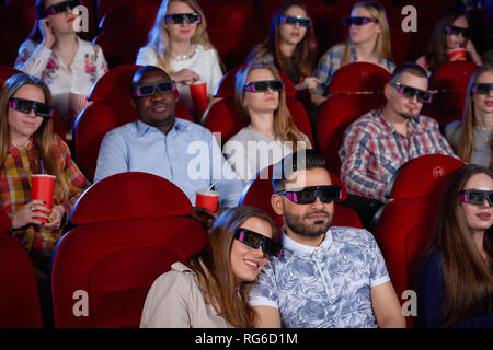 Couple Arabian man and brunette woman sitting together in cinema, embracing and watching comedy. Handsome man hugging beautiful girlfriend sitting near while movie review. Modern cinema hall. - Stock Photo