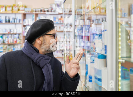 Old man in glasses looking at pharmacy shelf with medical products and pointing with fingers. Customer choosing medicines in drugstore. Man wearing in scarf, coat and male beret. - Stock Photo