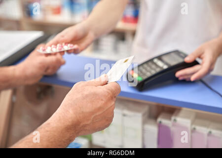Man showing credit card after making purchase using terminal. Payment machine on counter in drugstore. Pharmacist giving blister pack of pills to customer. - Stock Photo