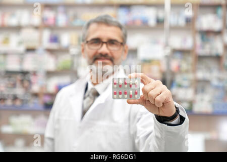 Chemist holding medicaments in hand, showing. Close up of blister pack of pills. Bearded pharmacist wearing in glasses and white lab coat. Professional specialist posing in drugstore. - Stock Photo