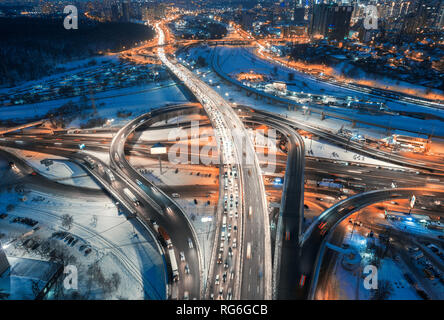 Aerial view of road in the modern city at night in winter. Top view of traffic in highway, buildings, illumination. Elevated road and Interchange over - Stock Photo