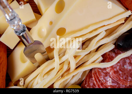Different kinds of cheese, olives and sausage meat and cheese plate - Stock Photo