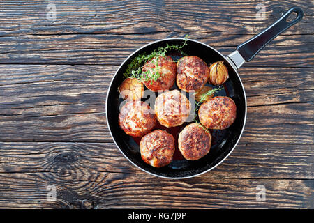 juicy delicious homemade fried turkey, chicken cutlets, patties of chopped meat in a skillet with thyme, garlic and onion on an old wooden table, view - Stock Photo