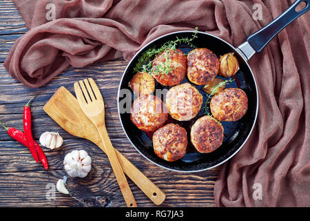homemade fried meat cutlets, patties of chopped meat in a skillet with thyme, garlic and onion on an old wooden table with brown cloth, view from abov - Stock Photo