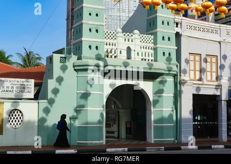 A Muslim woman about to enter Jamae Mosque in Chinatown, Singapore, the shadows of Chinese lanterns hanging over the street seen on the mosque wall - Stock Photo